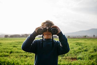 Spain, Barcelona. Boy in the field using binoculars. - p300m2275598 von Josep Rovirosa