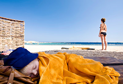 Boy sleeping on beach, woman on background - p312m1054694f by Stefan Isaksson