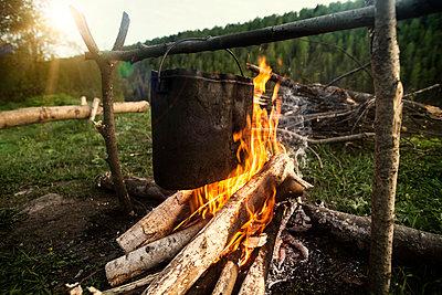 Food cooking over bonfire at campsite - p1166m1095728f by Cavan Images
