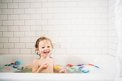 Portrait of cheerful girl bathing in bathtub against tiled wall - p1166m1543991 by Cavan Images