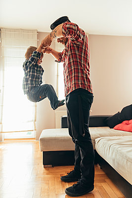 Father and son playing together at home - p300m1204800 by Zeljko Dangubic