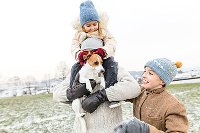 Happy father with two children and dog in winter landscape - p300m2080982 by Katharina Mikhrin
