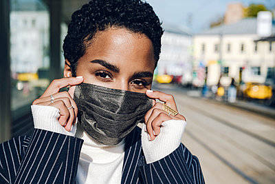 Young businesswoman wearing protective face mask at bus stop on sunny day - p300m2241373 by Katharina und Ekaterina