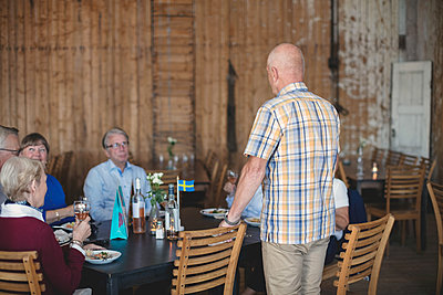 Senior man giving speech to friends while having lunch in restaurant - p426m1506308 by Maskot