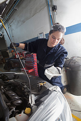 Hispanic mechanic checking oil in car engine - p555m1303359 by REB Images