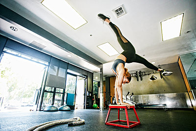 Mixed Race woman doing handstand on stool in gymnasium - p555m1304143 by Peathegee Inc
