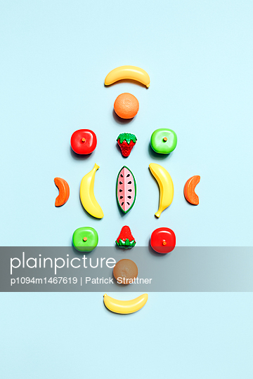 Directly above shot of various fruit toys arranged on blue background - p1094m1467619 by Patrick Strattner