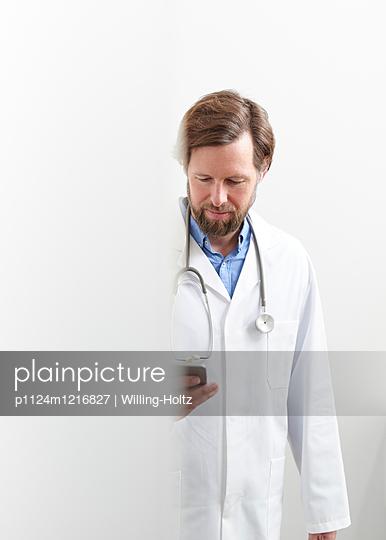 Junger Arzt mit Smartphone - p1124m1216827 von Willing-Holtz