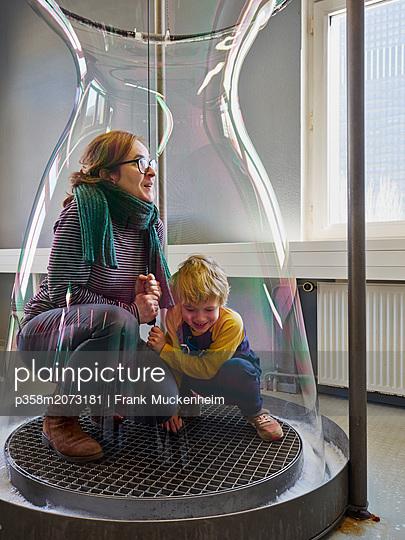 Mutter mit Sohn in Riesenseifenblase - p358m2073181 von Frank Muckenheim