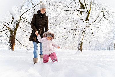 Happy mother walking with daughter in winter landscape - p300m2083324 von Daniel Ingold