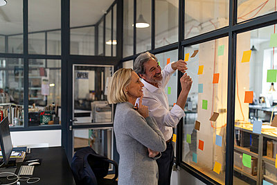 Happy colleagues looking at sticky notes at glass pane in office - p300m2143987 by Gustafsson