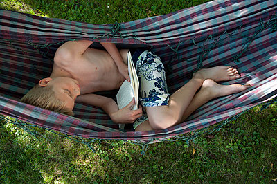 Boy reading book in hammock - p896m834550 by Sabine Joosten