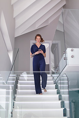 Young woman coming down modern stairway looking at smartphone - p924m2068865 by Bean Creative
