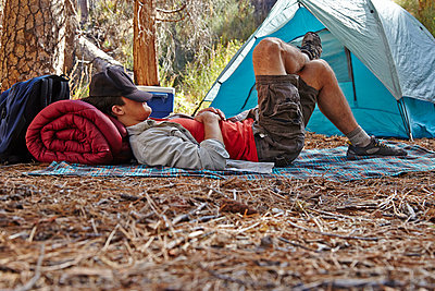 Young male camper resting in forest, Los Angeles, California, USA - p924m998764f by Tony Garcia