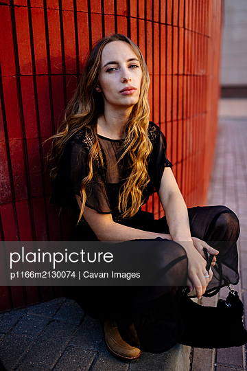 Woman sitting near a red wall in a black dress - p1166m2130074 by Cavan Images