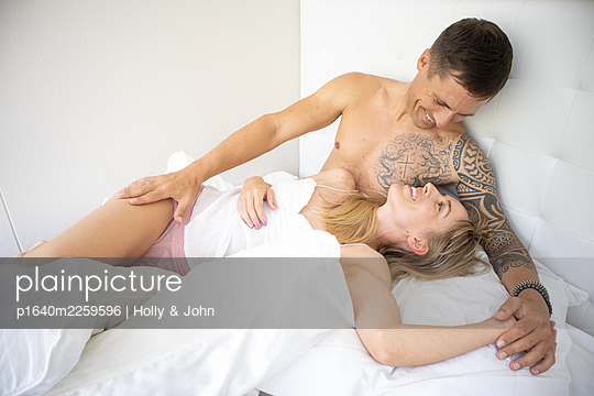 Couple in love embracing in bed - p1640m2259596 by Holly & John