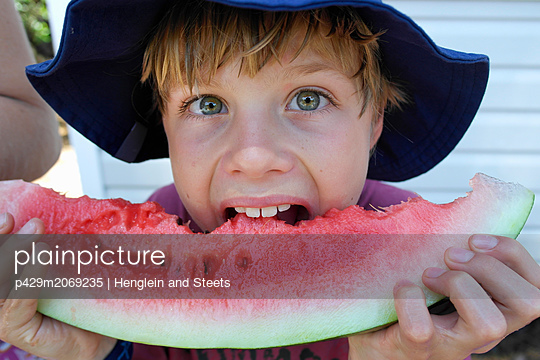 Boy biting into watermelon - p429m2069235 by Henglein and Steets