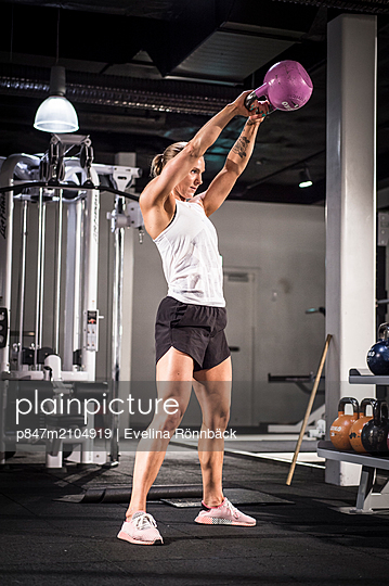 An Athletic Woman Exercising With Kettlebell In Gym   - p847m2104919 by Evelina Rönnbäck