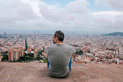 Rear view of man looking at cityscape while sitting on building terrace against cloudy sky - p1166m2034634 by Cavan Social