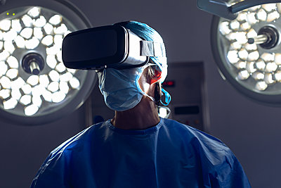 Male surgeon using virtual reality headset in operating room at hospital - p1315m2117699 by Wavebreak
