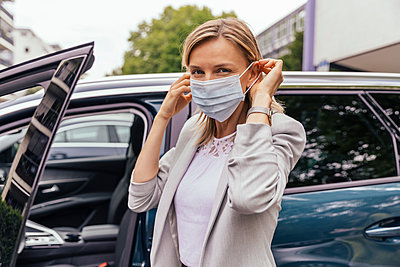 Portrait of woman standing in front of her car putting on protective mask - p300m2198669 by Mareen Fischinger