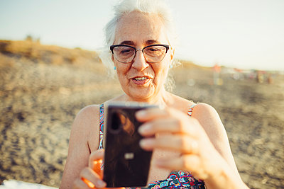 Smiling senior woman using mobile phone while standing at beach - p300m2221130 by Eugenio Marongiu