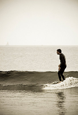 A surfer rides a wave on his longboard (desaturated color) - p3437618f by Jonathan Kingston