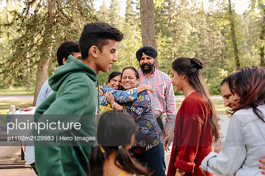 Indian family meeting in the park - p1192m2129983 by Hero Images