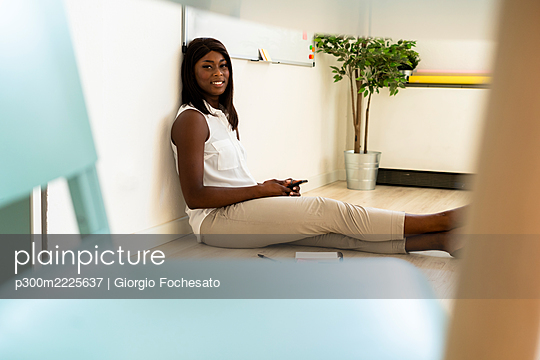 Smiling businesswoman using phone while sitting on floor at office - p300m2225637 by Giorgio Fochesato