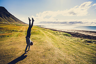 Woman doing handstand,West fjords, Iceland - p1084m986840 by Operation XZ