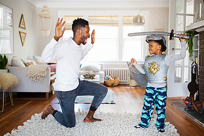 Father and son playing with sword at home - p1166m1140349 by Cavan Images