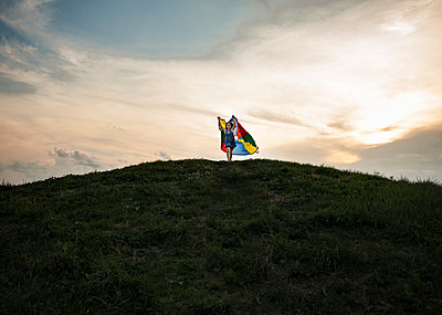 Low angle view of playful girl holding multi colored textile while running on hill against cloudy sky - p1166m1509617 by Cavan Images