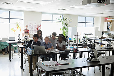 Middle school students conducting scientific experiment at laptop in science laboratory - p1192m1473265 by Hero Images
