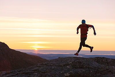 Person jogging at sunset - p312m1187756 by Niclas Vestefjell