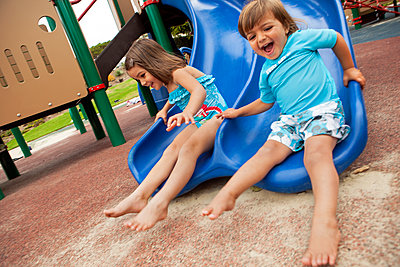 Brother and sister sliding down slide on playground - p555m1479298 by Jihan Abdalla