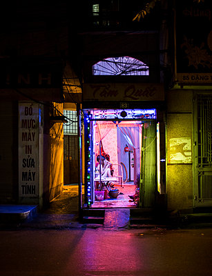 Open doorway of a massage shop along a dark street in Dong Da District Hanoi, Vietnam, Southeast Asia - p934m1071275 by Mathieu Arnaudet