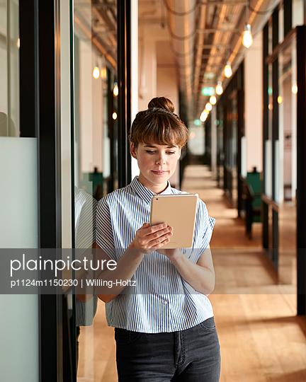 Junge Frau mit Tablet im Büroflur - p1124m1150230 von Willing-Holtz