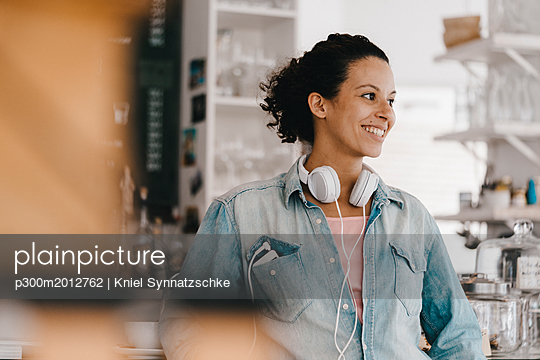 Young woman with headphones, working in coworking space - p300m2012762 von Kniel Synnatzschke