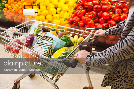 Midsection of woman pushing groceries in shopping cart at supermarket - p426m1017994f by Maskot