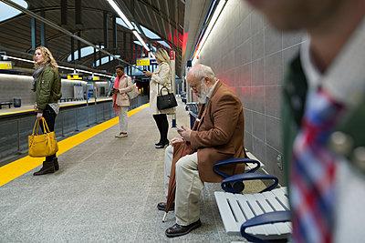 Senior man texting on bench subway station platform - p1192m1129715f by Hero Images