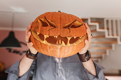 Man holding Jack O'Lantern in front of his face, smoke - p300m2059180 by Katharina Mikhrin