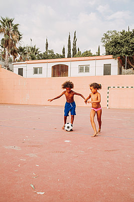 Two children playing soccer on a soccer field - p300m2132170 by DREAMSTOCK1982