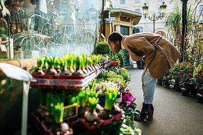 Woman smelling flowers at market in Paris, France - p300m2198473 by Kiko Jimenez