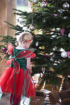 Young girl dressed up looking at the Christmas tree - p349m790658 by Polly Eltes