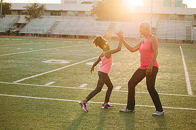 Grandmother and granddaughter high-fiving on football field - p555m1304768 by Shestock