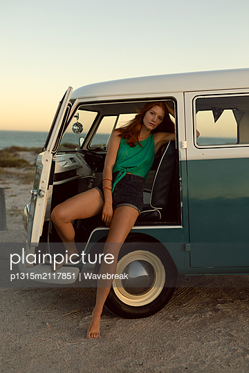 Beautiful woman looking at camera while sitting on front seat of camper van at beach - p1315m2117851 by Wavebreak