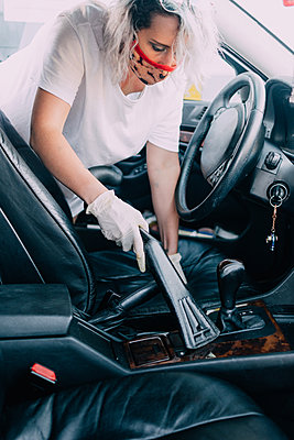 Woman cleans car interior with vacuum cleaner - p1166m2201514 by Cavan Images