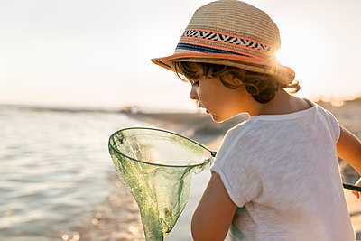 Spain, Menorca, little girl with a dip net on the beach - p300m1416883 by Marco Govel