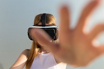 Young woman using Vr googles, reaching with her hand - p300m2140139 by Sus Pons