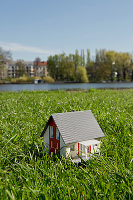 A miniature house on the lawn near the shore of a river - p301m844099f by Caspar Benson